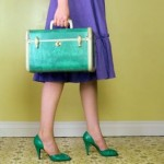 Woman carrying vintage suitcase --- Image by © Royalty-Free/Corbis